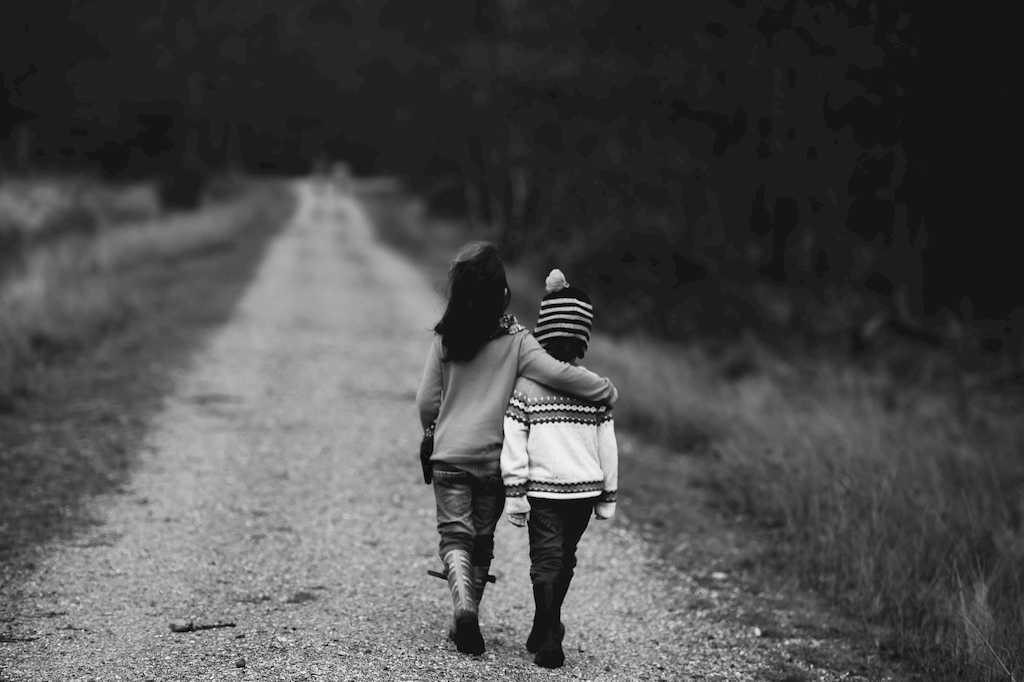一本道を肩を組んで歩いていく幼い兄弟